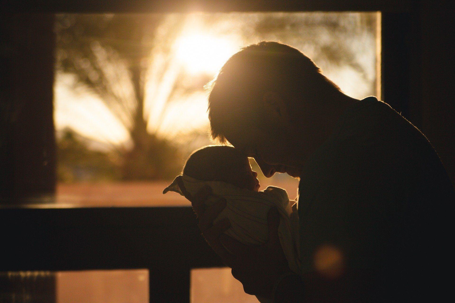 Ein Vater hält sein Neugeborenes in den Händen.