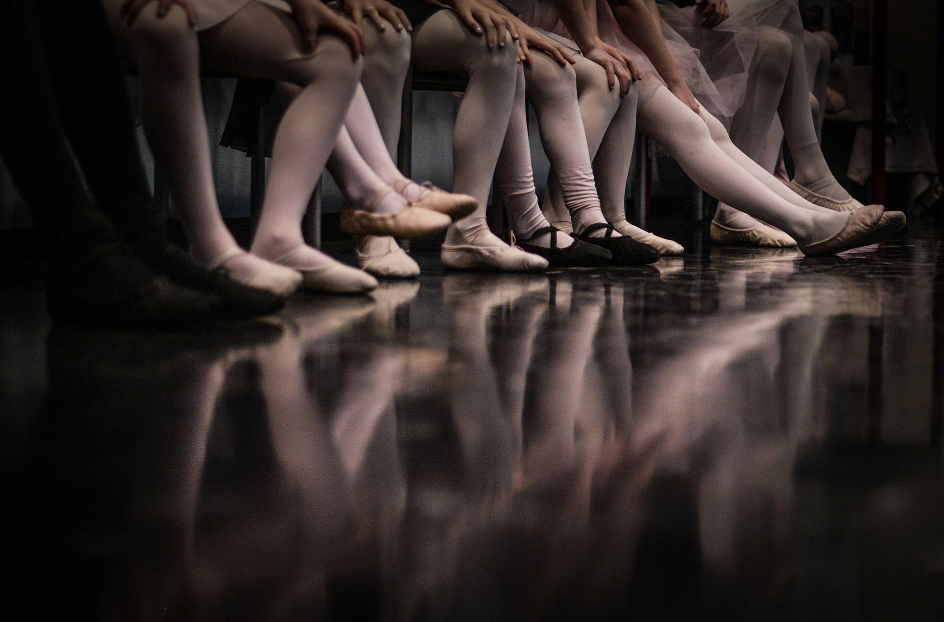 Eine Bank voll Kinderfüßen in Ballettschläppchen ist abgebildet.