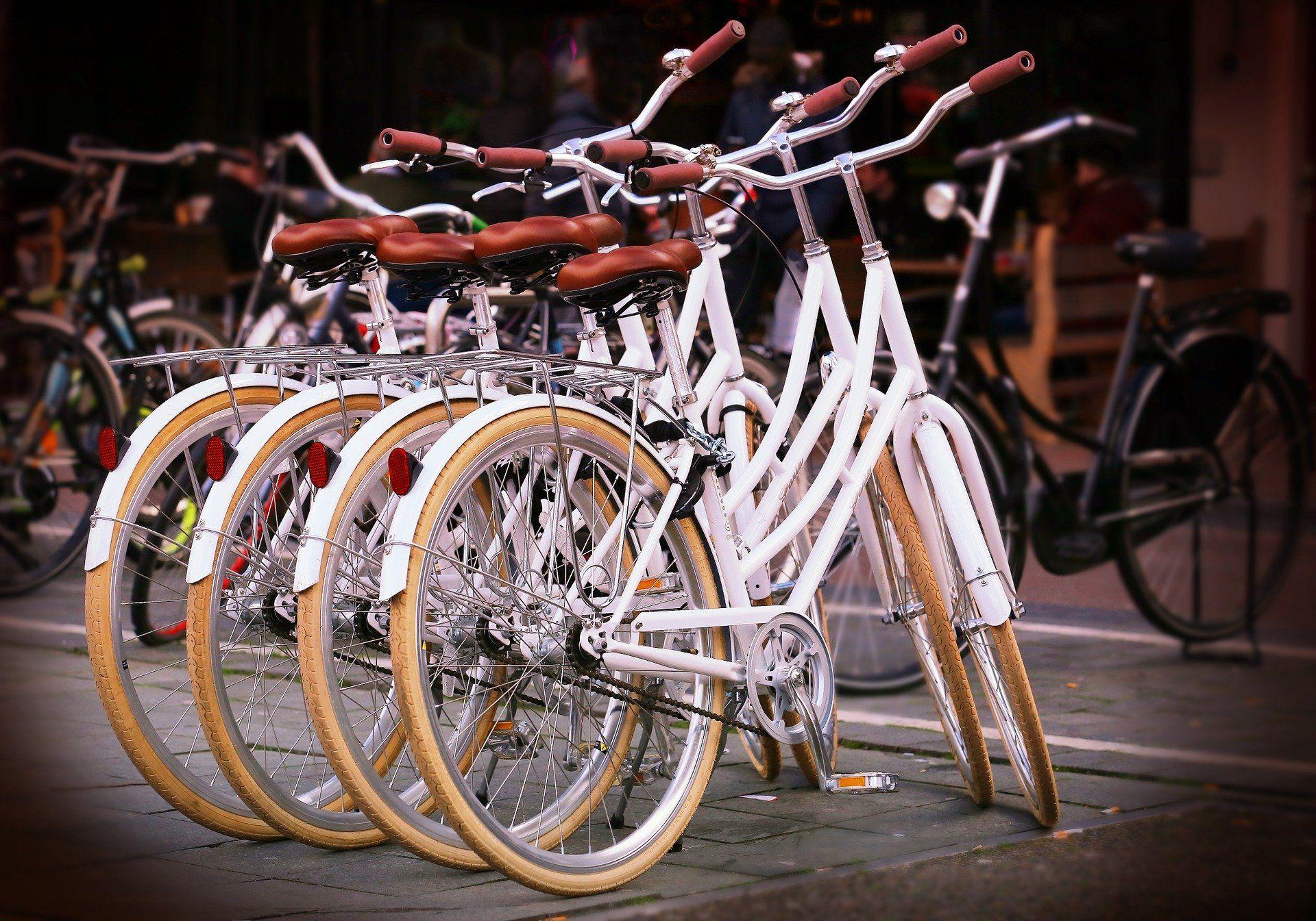 Vier Fahrräder stehen nebeneinander gereit auf der Straße.