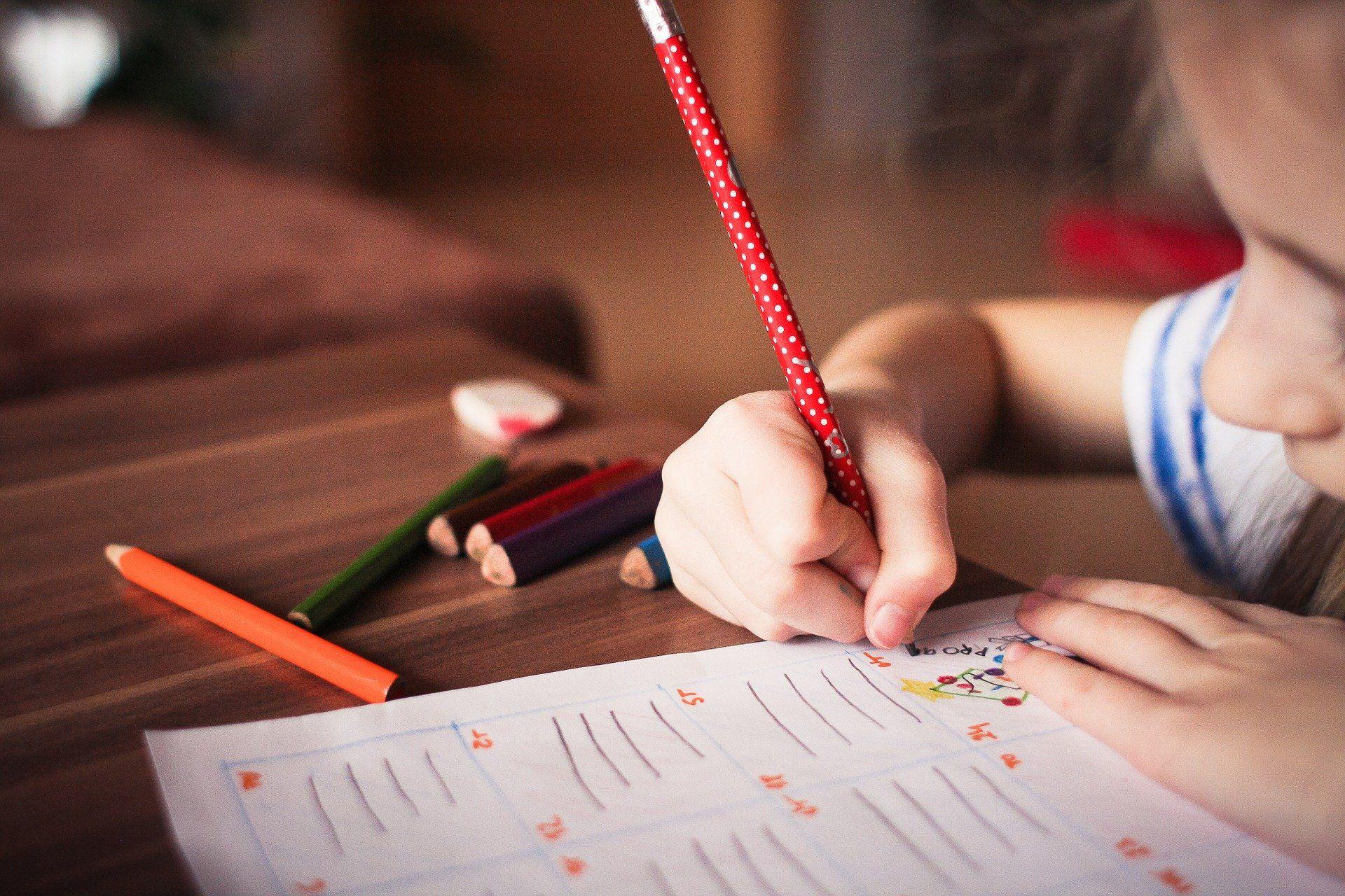 Ein Kind schreibt etwas auf ein Blatt Papier.
