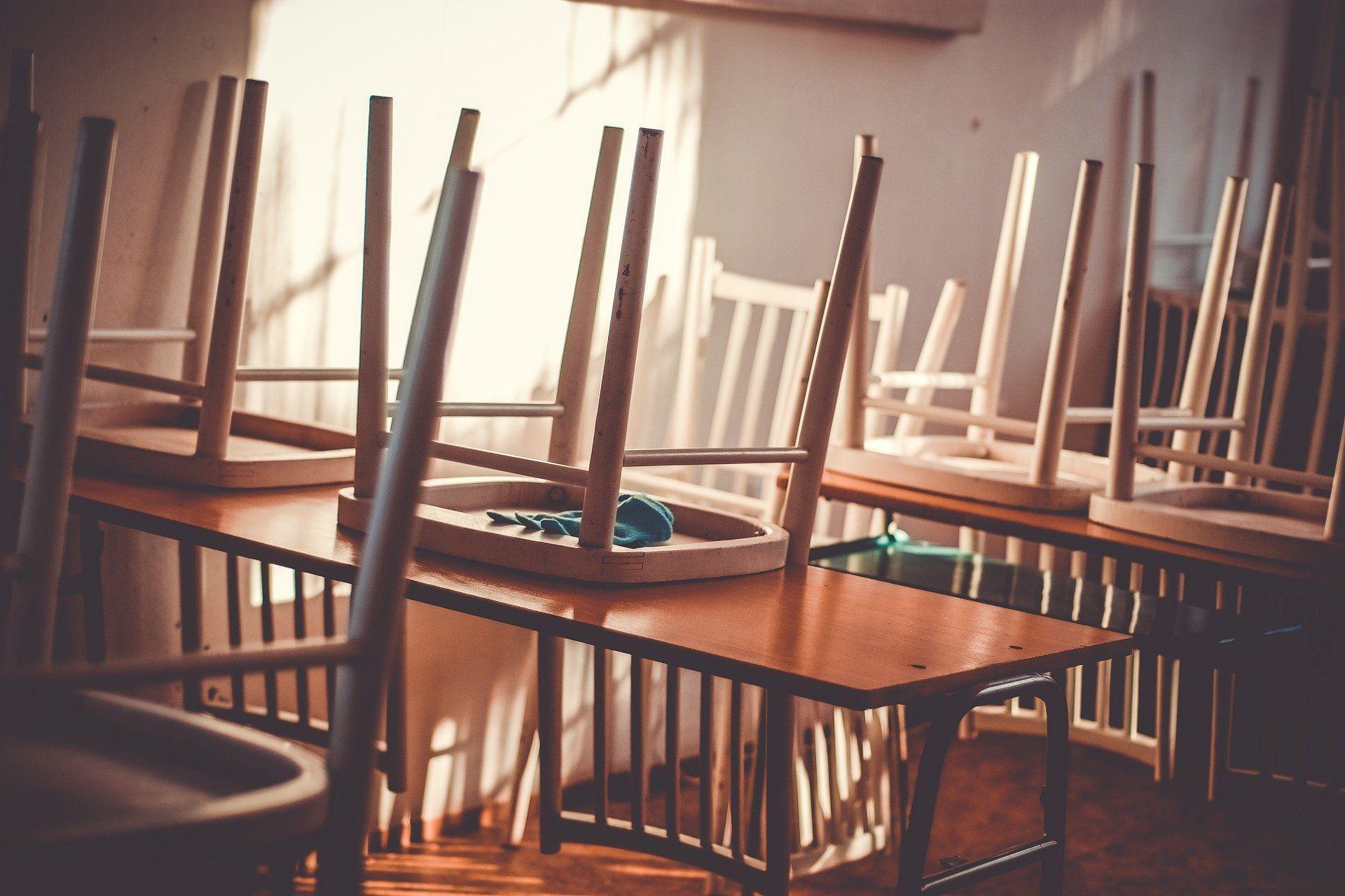 Es sind mehrere Schreibtische mit aufgestuhlten Stühlen hintereinander gereiht.