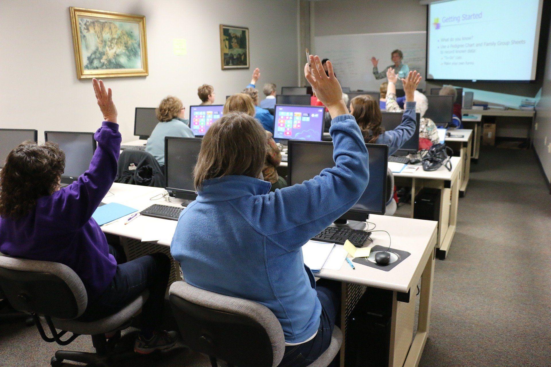 In einem Klassenzimmer sitzen Schüler vor Computern und melden sich.