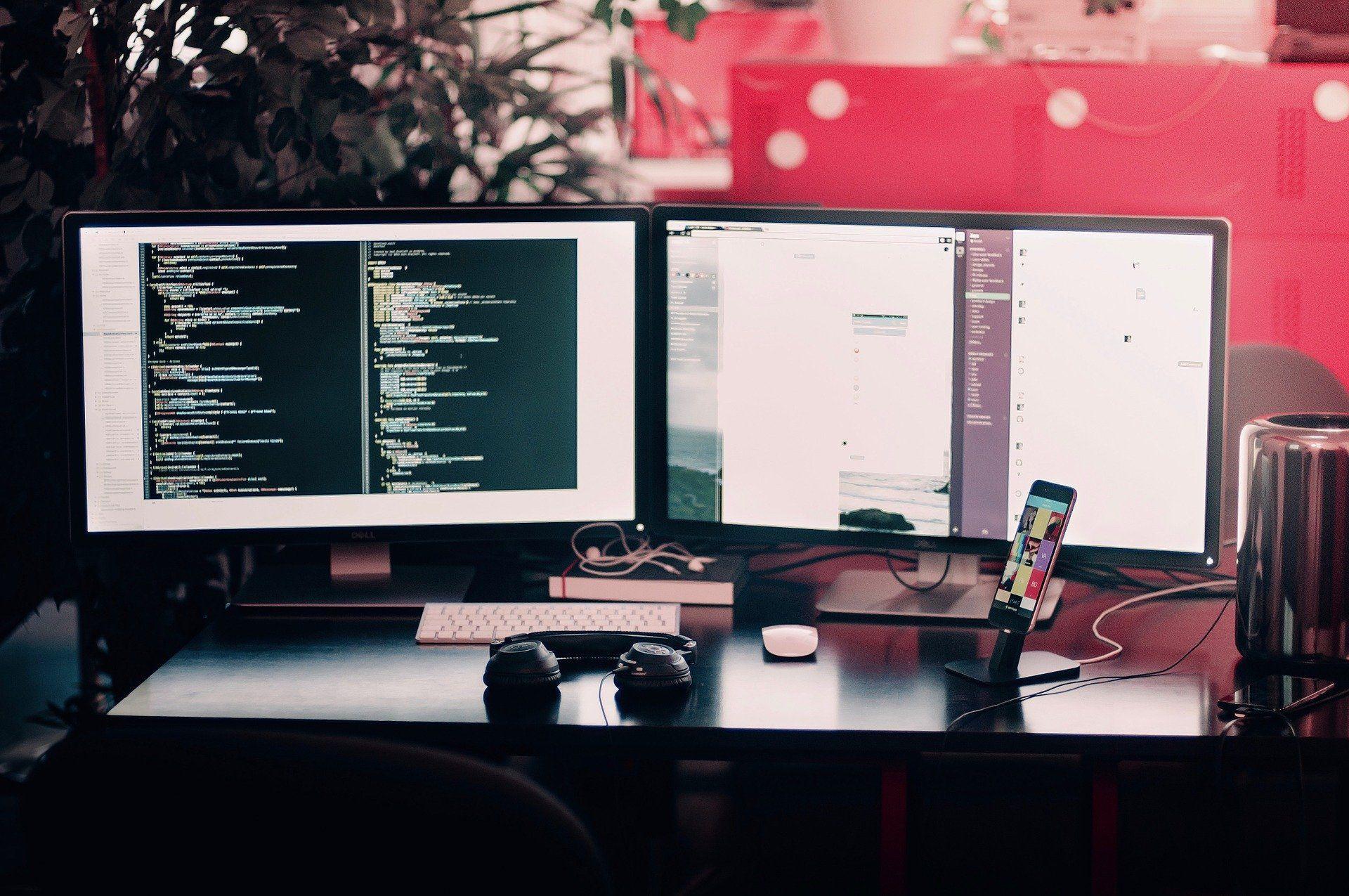 Auf einem Schreibtisch stehen zwei Computerbildschirme sowie ein Smartphone.