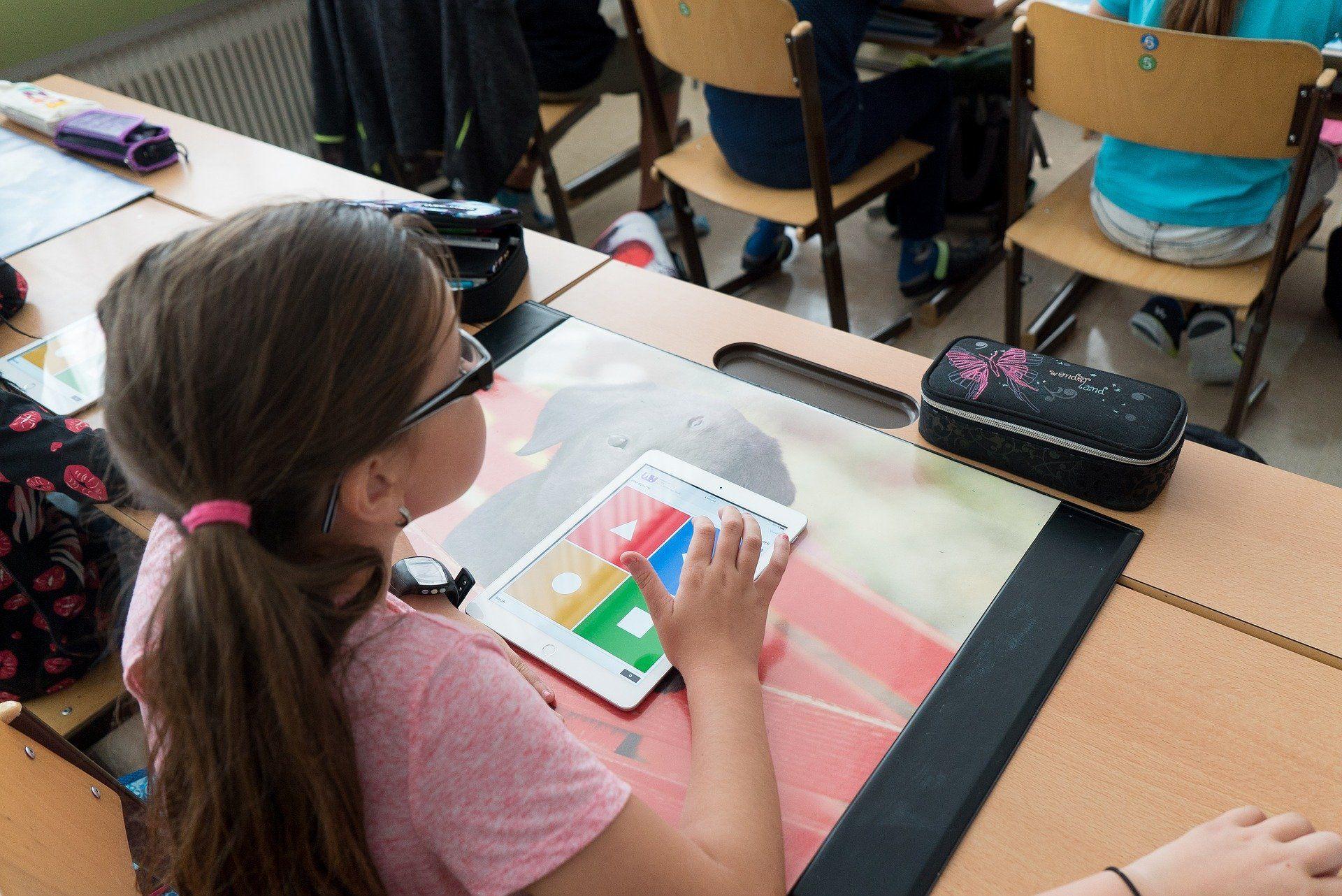 Ein Mädchen tippt etwas in ein Tablet ein.