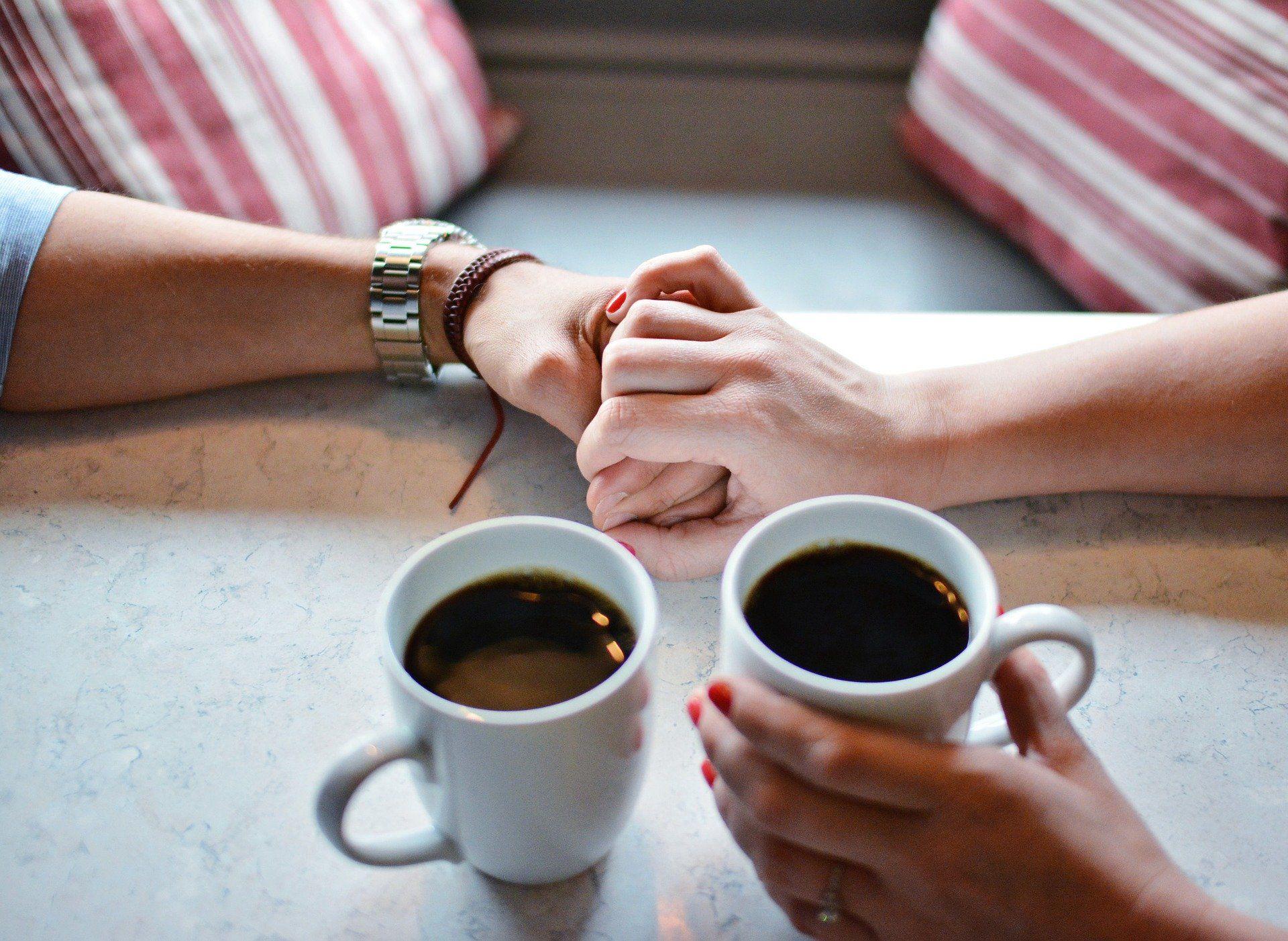 Zwei Tassen Kaffe stehen neben zwei sich haltenden Händen.