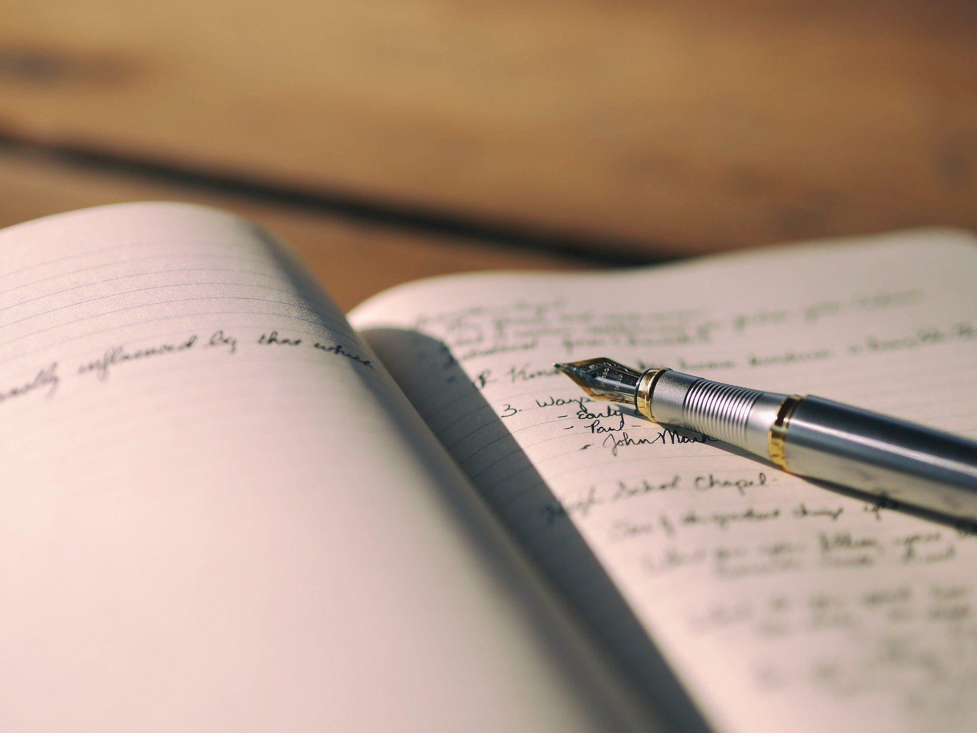 Ein Füller liegt auf der beschriebenen Seite eines aufgeschlagenen Notizbuches.
