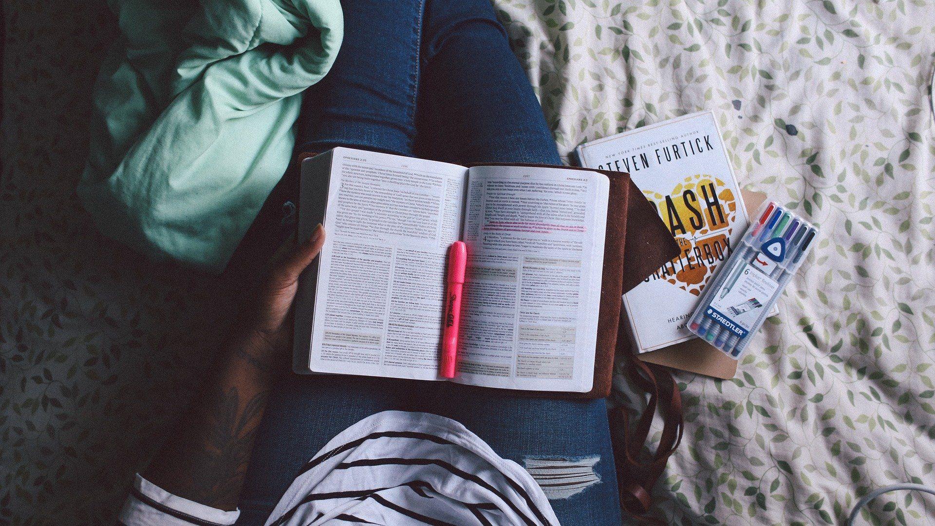 Eine Studentin hält ein Buch in ihrem Schoß.