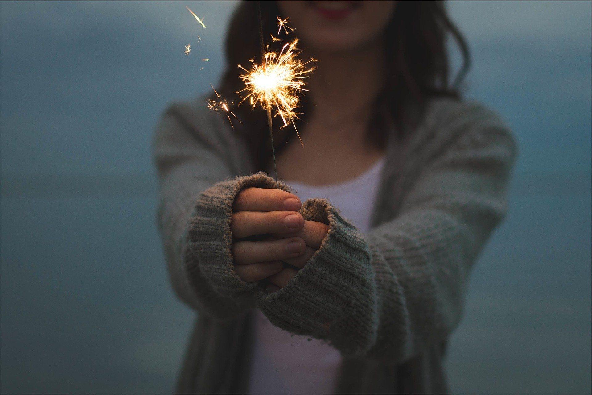 Ein Mädchen hält eine Wunderkerze in den Händen.