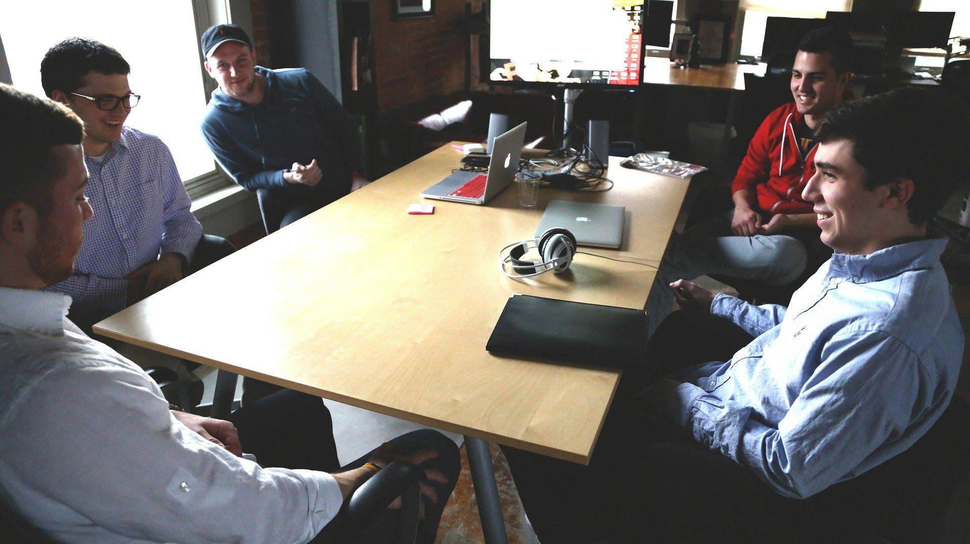 Mehrere Männer sitzen um einen Bürotisch herum.