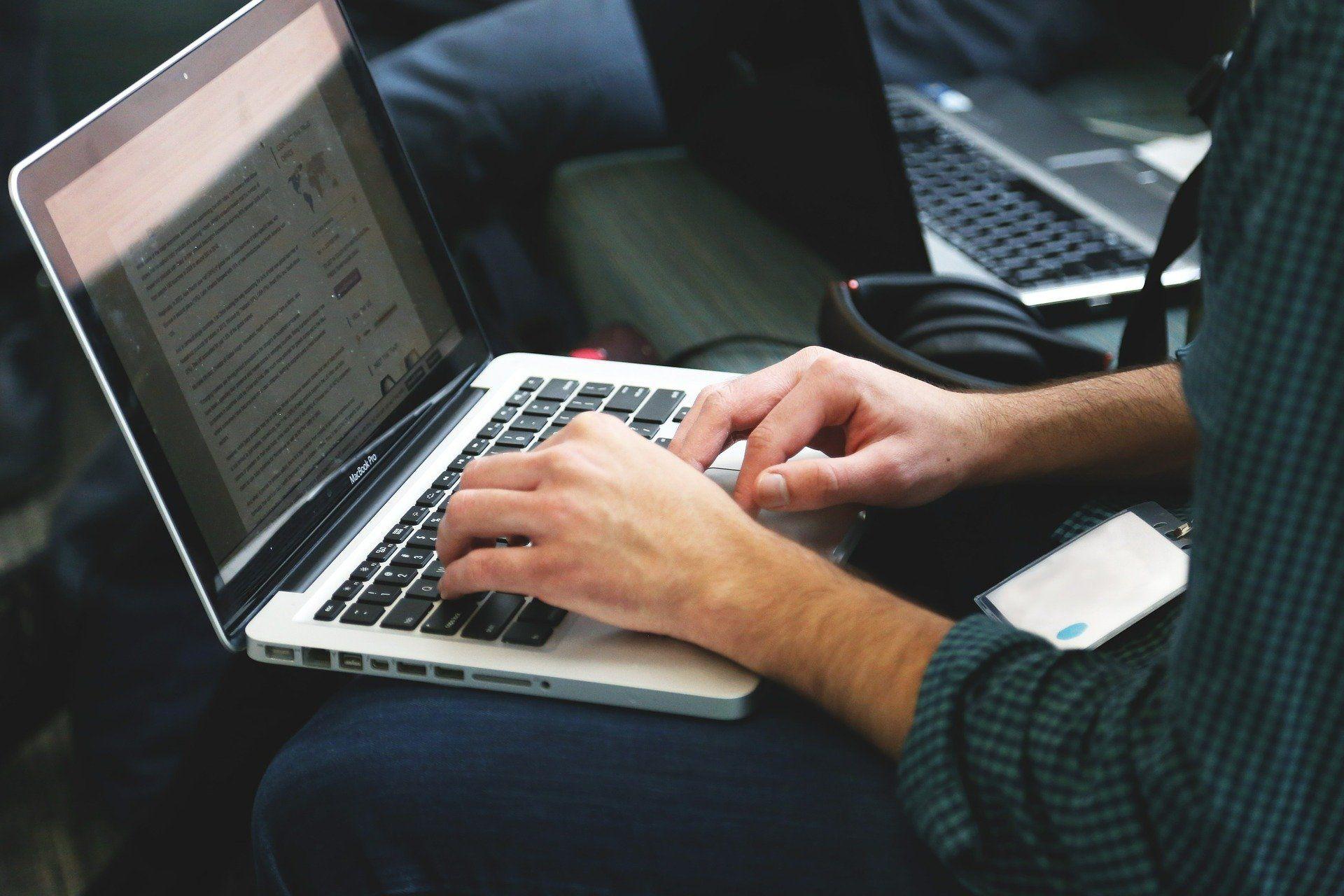 Ein Mann tippt etwas in seinen Laptop ein.