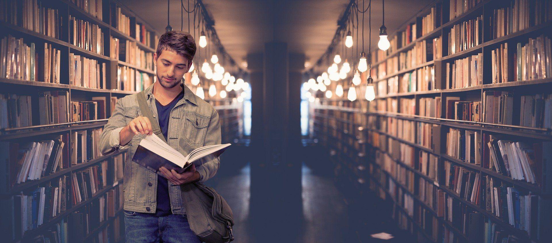 Ein junger Mann steht an einem Regal und blättert durch ein Buch.