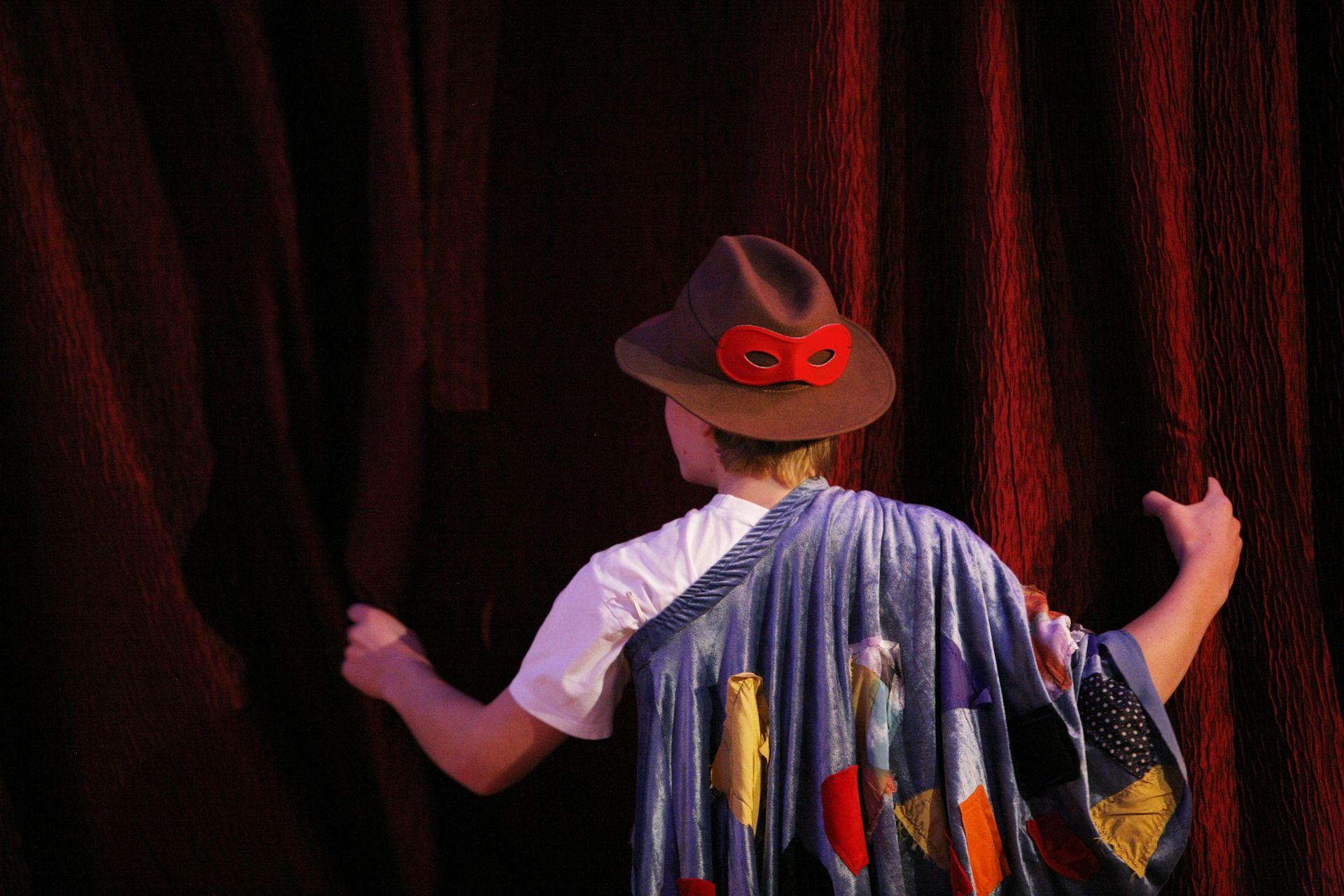 Ein verkleideter Junge steht vor einem roten Vorhang.