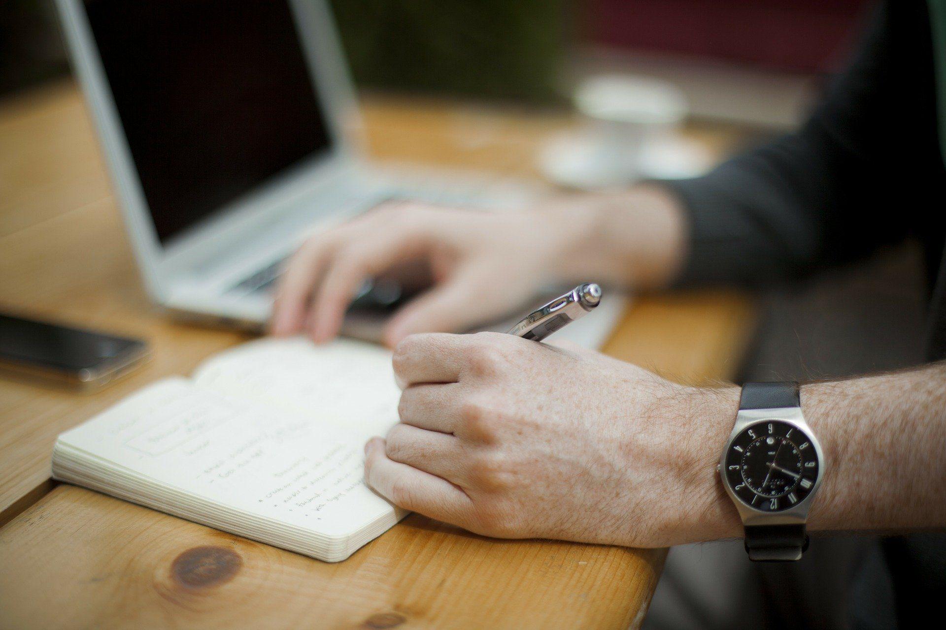 Eine Hand trägt etwas in ein Notizbuch ein.