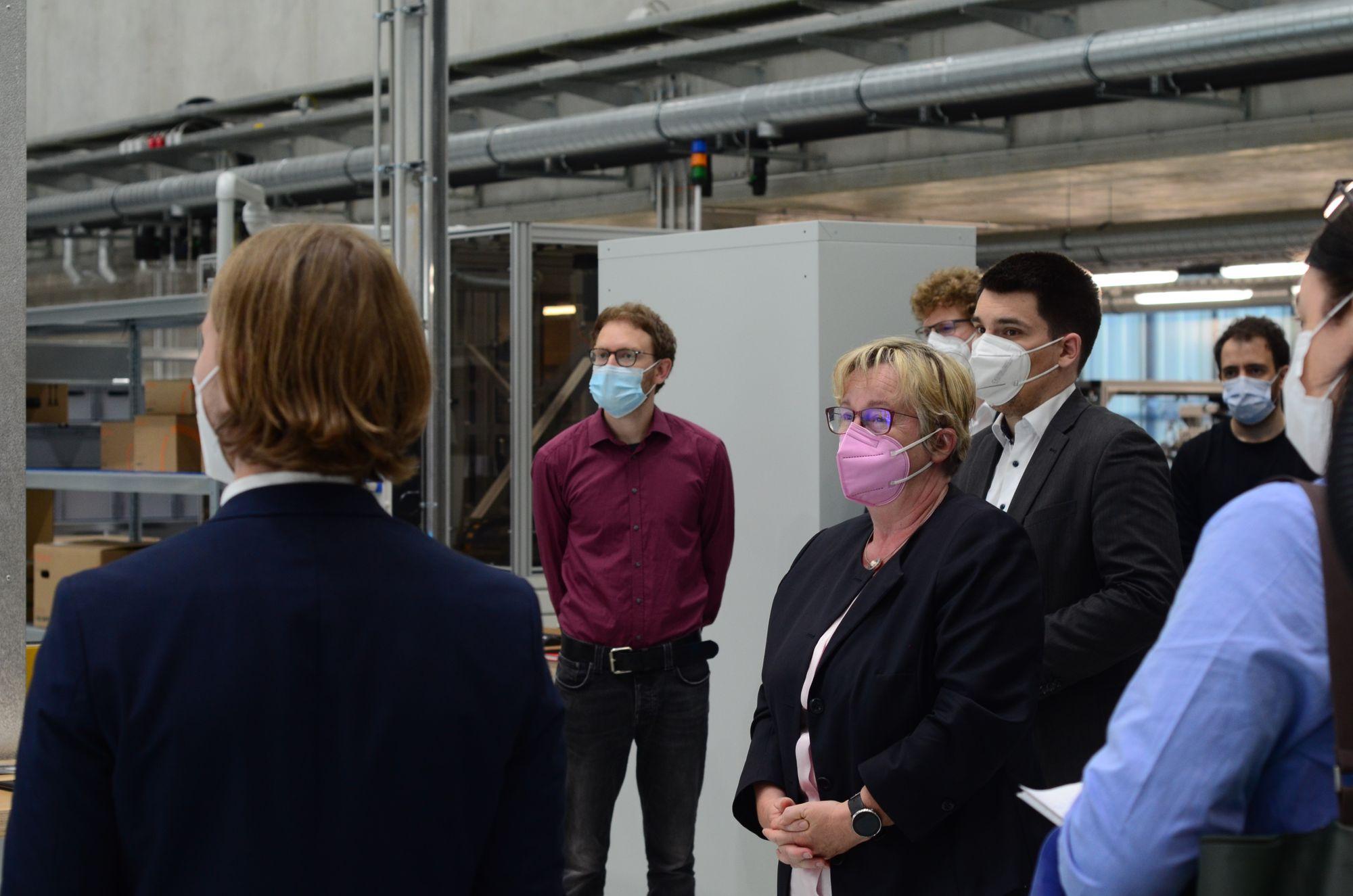 Ministerin Theresia Bauer und MdL Alexander Salomon stehen zwischen Wissenschaftler:innen in der Forschungshalle.