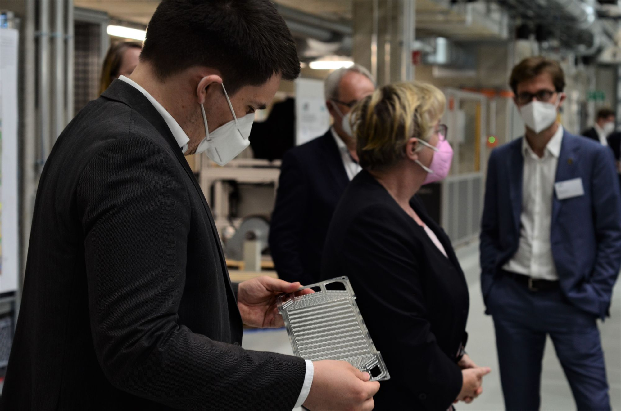 MdL Alexander Salomon hält ein Anschauungsobjekt in der Hand. Im Hintergrund ist Ministerin Bauer zu sehen, die sich mit weiteren Besucher:innen unterhölt.